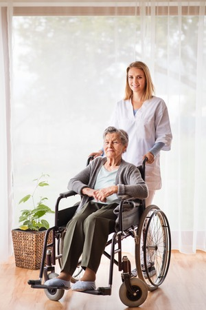 Foto de Health visitor and a senior woman during home visit. - Imagen libre de derechos