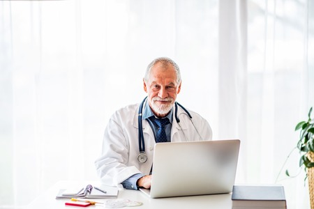 Photo for Senior doctor with laptop working at the office desk. - Royalty Free Image