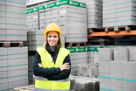 Foto de Woman worker standing in an industrial area. - Imagen libre de derechos