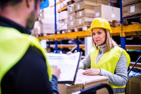 Photo for Young warehouse workers working together. - Royalty Free Image