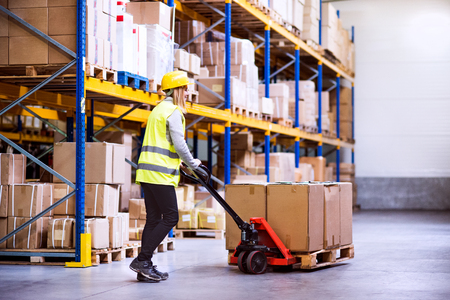 Photo for Woman warehouse worker with hand forklift truck. - Royalty Free Image