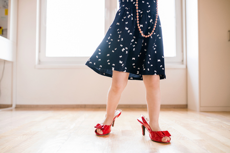 Photo for Unrecognizable little girl in dress and red high heels at home. - Royalty Free Image
