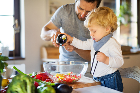 Photo pour Young father with a toddler boy cooking. - image libre de droit