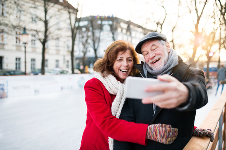 Photo for Senior couple with smartphone on a walk in a city in winter. - Royalty Free Image
