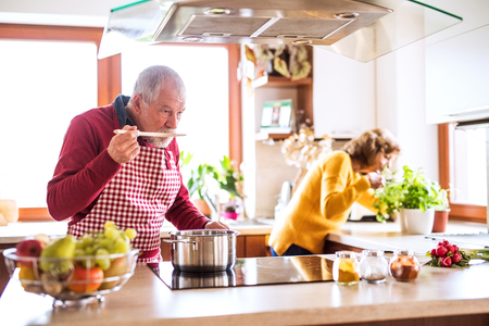 Foto de Senior couple preparing food in the kitchen. - Imagen libre de derechos