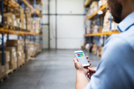Photo pour Unrecognizable man warehouse worker with a smartphone. - image libre de droit
