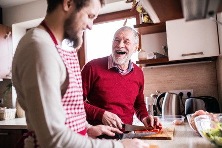 Photo pour Hipster son with his senior father cooking in the kitchen. - image libre de droit