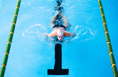 Photo for Senior man swimming in an indoor swimming pool. - Royalty Free Image