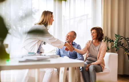 Photo for Female doctor talking to a senior couple. - Royalty Free Image