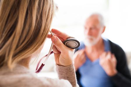 Foto de Health visitor and a senior man during home visit. - Imagen libre de derechos