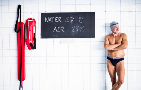 Foto de Senior man standing in an indoor swimming pool. - Imagen libre de derechos