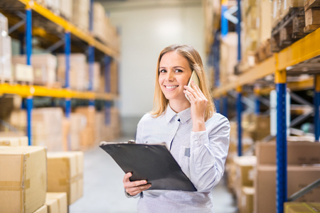 Photo pour Woman warehouse worker or supervisor with smartphone. - image libre de droit