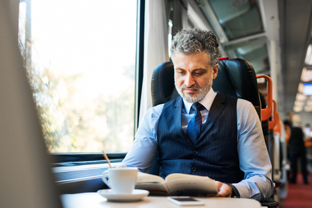 Foto per Mature businessman travelling by train. - Immagine Royalty Free