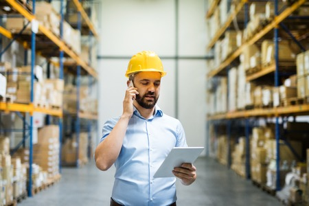 Photo for Warehouse worker or supervisor with a smartphone. - Royalty Free Image