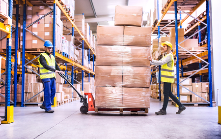 Photo for Warehouse workers pulling a pallet truck. - Royalty Free Image