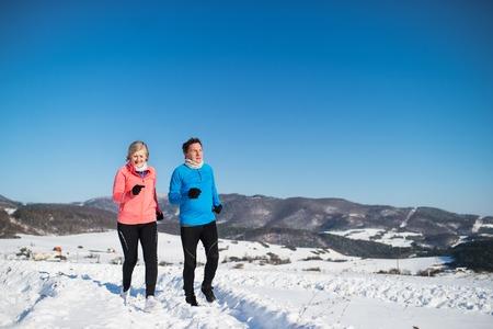 Photo pour Senior couple jogging in winter nature. - image libre de droit