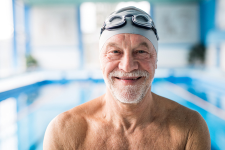 Photo pour Senior man standing in an indoor swimming pool. - image libre de droit