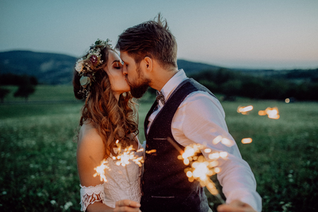 Foto de Beautiful bride and groom with sparklers on a meadow. - Imagen libre de derechos