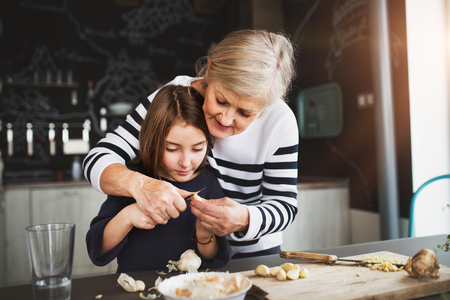 Foto de A small girl with grandmother cooking at home. - Imagen libre de derechos