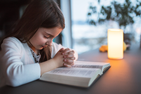 Photo pour A small girl praying at home. - image libre de droit