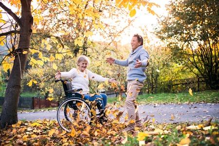 Foto de Senior couple in wheelchair in autumn nature. - Imagen libre de derechos