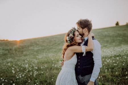 Foto de Beautiful bride and groom at sunset in green nature. - Imagen libre de derechos