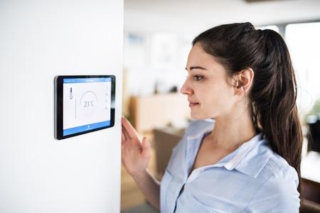 Foto für A woman looking at tablet with smart home screen. - Lizenzfreies Bild