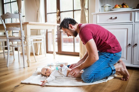 Photo for Father changing a baby girl at home. - Royalty Free Image