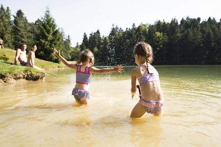 Foto de Mother, father and daughters at the lake. Sunny summer. - Imagen libre de derechos