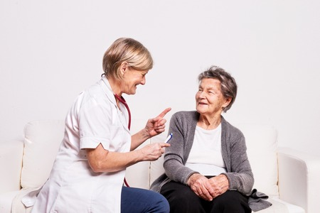 Foto de Studio portrait of a senior nurse examining an elderly woman. - Imagen libre de derechos