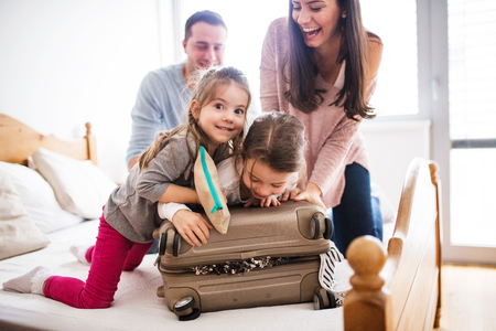 Photo pour Young family with two children packing for holiday. - image libre de droit