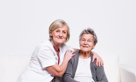 Foto de Studio portrait of a senior nurse and an elderly woman. - Imagen libre de derechos