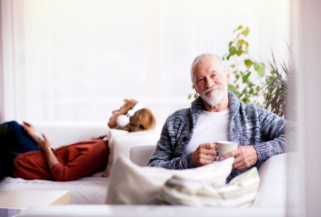 Photo for Senior couple sitting on the sofa and relaxing at home. - Royalty Free Image