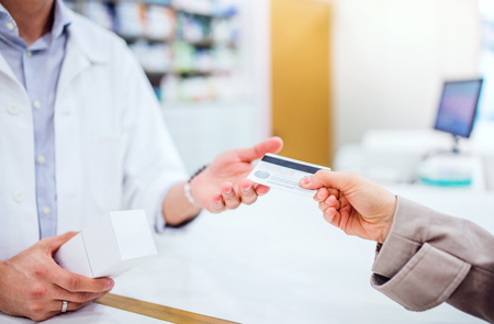 Photo pour Unrecognizable customer giving a credit card to a male pharmacist. - image libre de droit