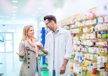 Foto de Male pharmacist serving a female customer. - Imagen libre de derechos