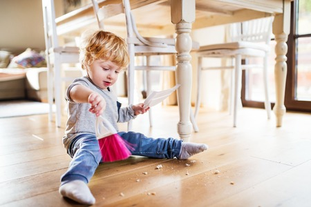 Foto de A toddler boy with brush and dustpan at home. - Imagen libre de derechos