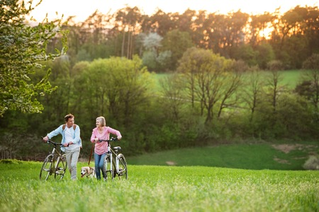 Photo pour Beautiful senior couple with bicycles and dog outside in spring nature. - image libre de droit