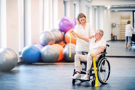 Photo for Young woman physiotherapist working with a senior man in wheelchair. - Royalty Free Image