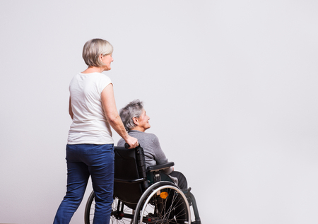 Foto de Studio portrait of a senior woman in wheelchair with a carer. - Imagen libre de derechos
