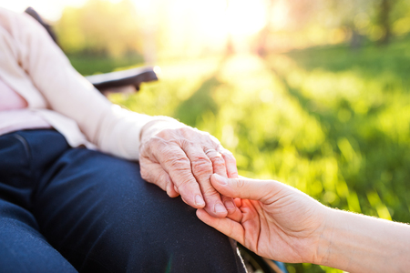 Photo for Granddaughter holding hand of grandmother in wheelchair in spring nature. - Royalty Free Image