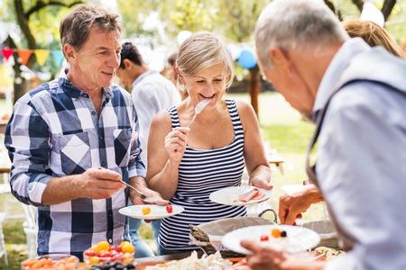 Foto de Family celebration or a garden party outside in the backyard. - Imagen libre de derechos