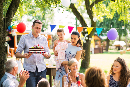 Photo for Family celebration or a garden party outside in the backyard. - Royalty Free Image