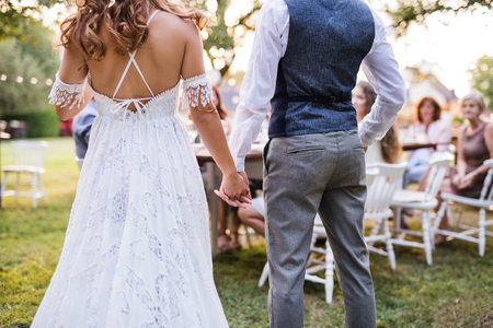 Photo pour Unrecognizable bride and groom with guests at wedding reception outside in the backyard. - image libre de droit
