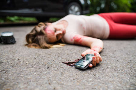Photo for Young injured woman with smartphone lying on the road after a car accident, unconscious. - Royalty Free Image