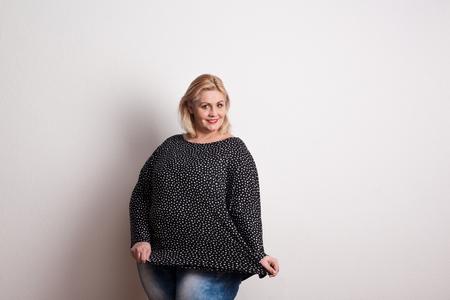 Foto de A happy attractive overweight woman in studio on a white background. - Imagen libre de derechos