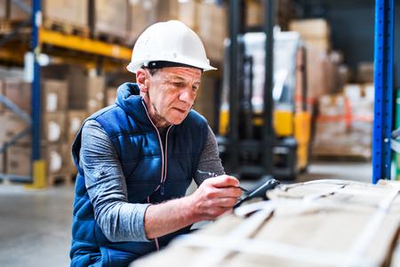 Foto de Portrait of a senior male warehouse worker or a supervisor. - Imagen libre de derechos