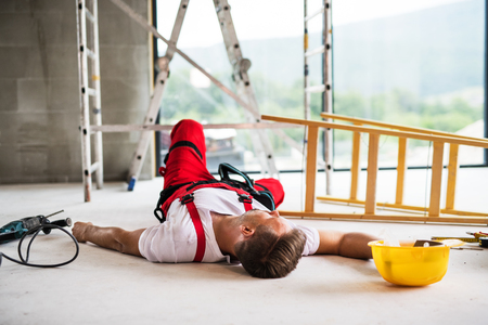 Foto de A man worker lying on the floor after an accident at the construction site. - Imagen libre de derechos