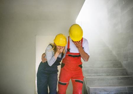 Foto de Woman and man workers suffocating at the construction site. - Imagen libre de derechos
