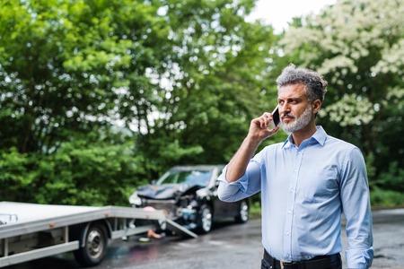 Photo pour Mature man making a phone call after a car accident. Copy space. - image libre de droit