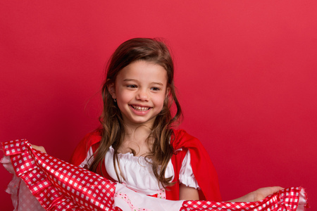 Photo for A small girl in Little Red Riding Hood costume in studio on a red background. - Royalty Free Image